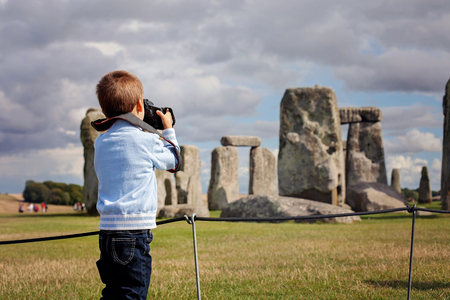 Photo for Young child, boy, taking pic with digital camera at Stonehenge on a cloudy day - Royalty Free Image