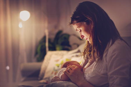 Photo pour Young beautiful mother, breastfeeding her newborn baby boy at night, dim light. Mom breastfeeding infant - image libre de droit