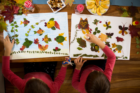 Photo for Sweet children, boys, applying leaves using glue while doing arts and crafts in school, autumn time - Royalty Free Image