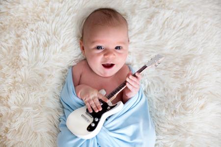 Foto de Newborn baby boy, wrapped in blue scarf, holding a little guitar and smiling - Imagen libre de derechos