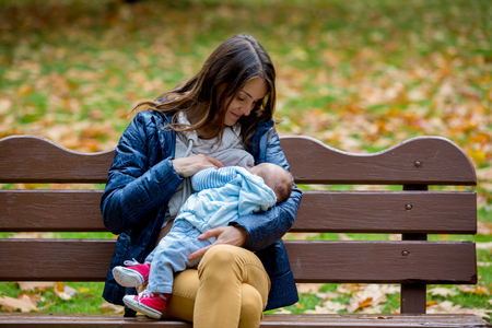 Photo for Young mother, breastfeeding her newborn baby boy outdoor in the park, autumn time - Royalty Free Image