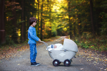 Foto de Sweet preschool boy pushing his little newborn baby boy, sleeping in old retro stroller in forest, autumn time, wrapped in scarf and knitted hat. Posed baby, retro pram, infant, vintage stroller - Imagen libre de derechos