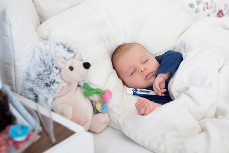 Photo for Cute newborn baby boy, lying in bed with cold and fever - Royalty Free Image