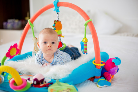 Photo pour Cute baby boy on colorful gym, playing with hanging toys at home, baby activity and play center for early infant development. Kids playing at home - image libre de droit