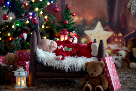 Photo pour Portrait of newborn baby in Santa clothes in little baby bed, sleeping under Christmas tree, winter snow landscape outdoor - image libre de droit