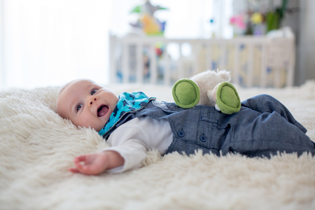 Photo pour Little cute baby boy, playing with toys at home, smiling at camera, wintertime - image libre de droit