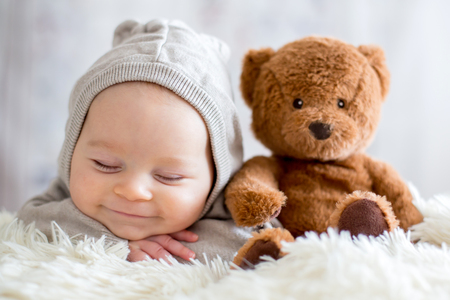 Foto de Sweet baby boy in bear overall, sleeping in bed with teddy bear stuffed toys, winter landscape behind him - Imagen libre de derechos