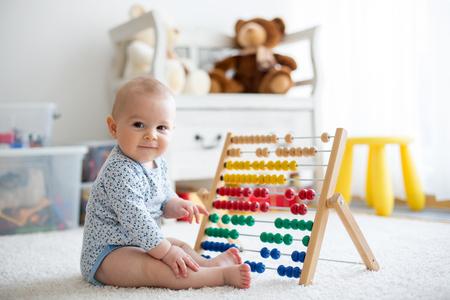 Foto de Cute little baby boy, playing with abacus at home, sunny kids room - Imagen libre de derechos