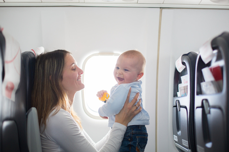Foto de Young mom, playing and breastfeeding her toddler boy on board of aircraft, going on holiday - Imagen libre de derechos