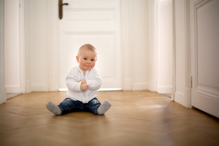 Photo for Little baby boy, toddler, in a long hall, crawling on the floor, smiling - Royalty Free Image