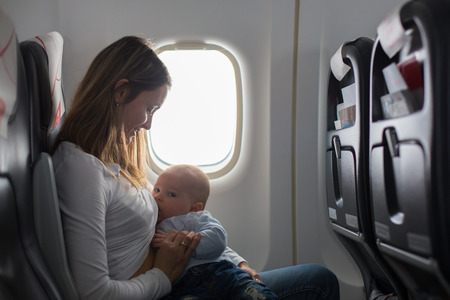 Photo for Young mom, playing and breastfeeding her toddler boy on board of aircraft, going on holiday - Royalty Free Image