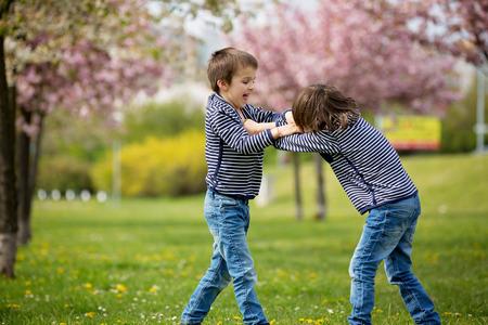 Foto de Two children, brothers, fighting in a park, springtime - Imagen libre de derechos