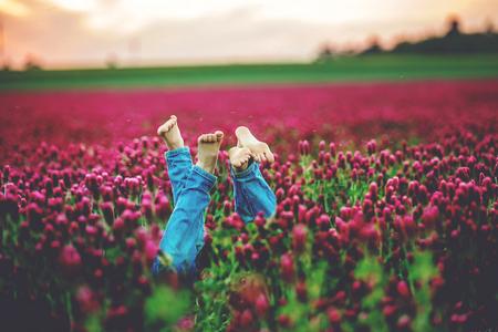 Photo pour Beautiful children in gorgeous crimson clover field on sunset, springtime. Kids feet seen over the flowers - image libre de droit