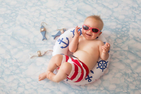Photo pour Cute baby boy lying down on a tiny inflatable swim ring,  wearing swimsuit shorts and sunglasses, indoor shot - image libre de droit