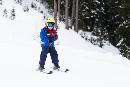 Photo pour Young child, going up a hill with a surface lift, standing on the ground, using button ski lift. Little skier, learning in winter school in an Austrian resort - image libre de droit