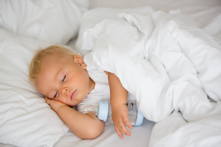 Photo pour Cute little baby boy, sleeping with bottle with formula milk. Tired child in baby cot bed - image libre de droit