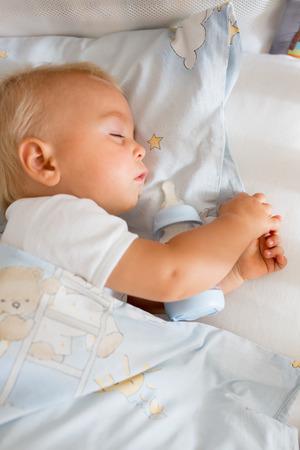 Foto de Cute little baby boy, sleeping with bottle with formula milk. Tired child in baby cot bed - Imagen libre de derechos