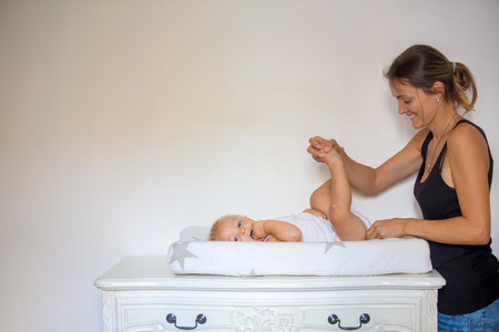 Photo pour Happy mother playing with baby while changing his diaper. Smiling young woman with baby son on changing table at home. Close up of cheerful mom and toddler boy playing together. - image libre de droit