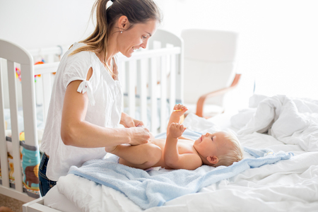 Photo pour Young mom, changing baby diaper after bath in sunny bedroom - image libre de droit