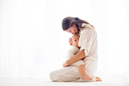 Photo pour Young mother breastfeeding her toddler baby boy at home - image libre de droit