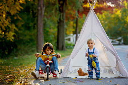 Foto de Children, sitting in a tent teepee, holding teddy bear toy with a nature autumn background in the park, imagination or happiness concept - Imagen libre de derechos