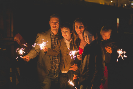 Photo for Waist up portrait of happy family celebrating New Year together and lighting sparklers outdoors in garden - Royalty Free Image
