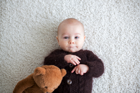 Photo pour Little cute baby boy, dressed in handmade knitted brown teddy bear overall, playing at home in sunny bedroom - image libre de droit