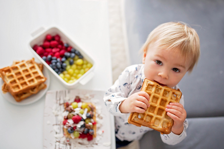 Photo for Sweet toddler birthday boy, eating belgian waffle with raspberries, blueberries, coconut and chocolate at home - Royalty Free Image