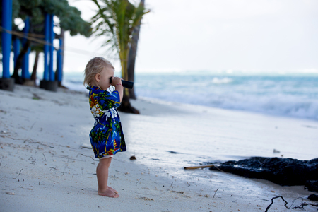 Foto de Sweet boy looks through binoculars, observating the ocean life and waves on sunset - Imagen libre de derechos