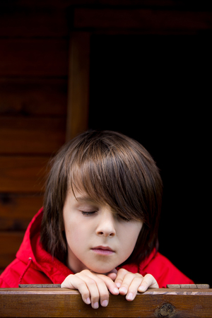Photo for Preteen boy in red sweatshirt, hiding behind a wooden door, looking scared and sad - Royalty Free Image
