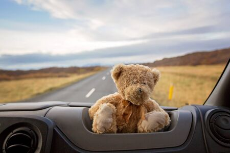 Foto de Teddy bear, sitting on the front windshield of a camper van, people traveling in Iceland, camping, autumntime - Imagen libre de derechos