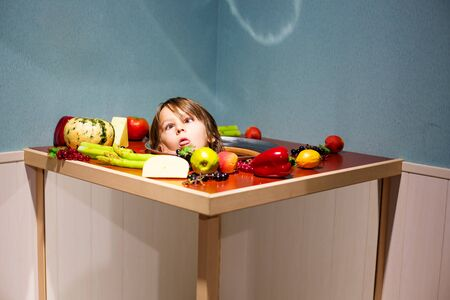 Foto de Kid, boy playing in a funny panel with plate and vegetables and his head on the plate - Imagen libre de derechos