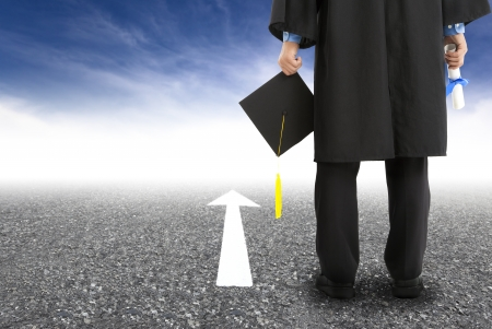 graduate standing on the road and forward arrow