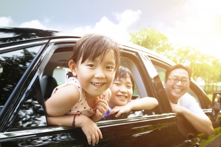 Photo for happy little girl with family sitting in the car  - Royalty Free Image
