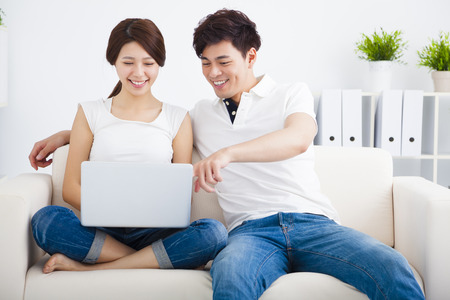 Foto per asian Couple on sofa with laptop computer - Immagine Royalty Free