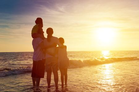 Photo for happy family watching the sunset on the beach - Royalty Free Image