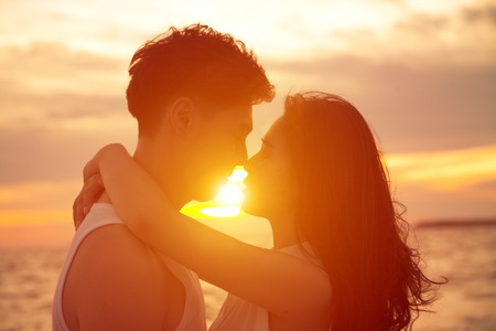 Photo for young couple kissing at sunset on beach - Royalty Free Image