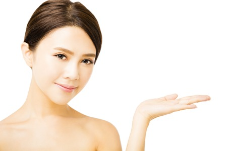 Photo for beautiful young woman showing beauty product empty  space on  hand - Royalty Free Image