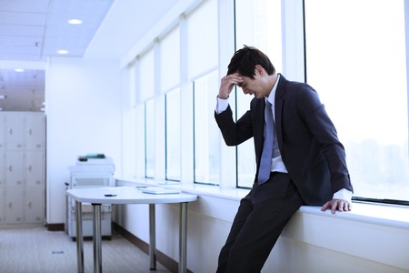 Depressed young businessman in office