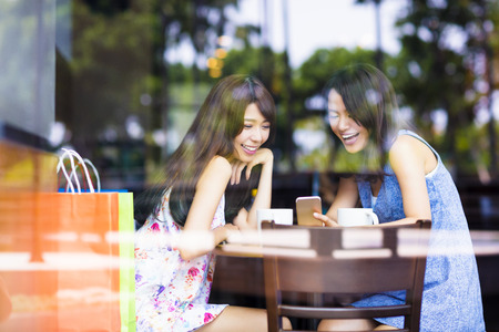 Photo for happy young woman looking at phone in coffee shop - Royalty Free Image