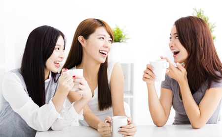 Photo for three happy young woman chatting in living room - Royalty Free Image