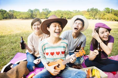 Photo for happy young friends enjoying picnic and playing ukulele - Royalty Free Image