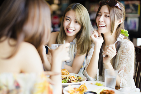 Photo for happy female friends sitting and chatting in restaurant - Royalty Free Image