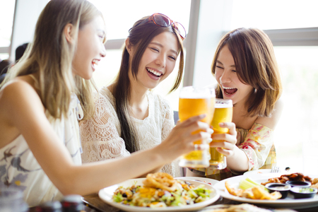 Photo for happy Group of girl friends toasting and eating in the  restaurant - Royalty Free Image