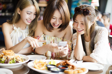 Photo for happy friends with smart phones taking picture in restaurant - Royalty Free Image