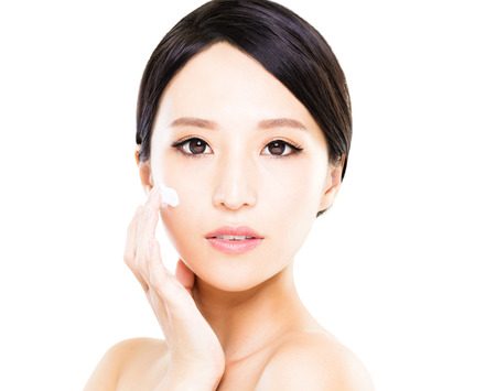 Photo for Beautiful women applying moisturizer cosmetic cream on face - Royalty Free Image