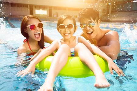 Foto per Happy family playing in swimming pool - Immagine Royalty Free