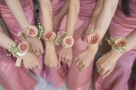 Photo pour close up of hands bridesmaid with flower and pink dress - image libre de droit