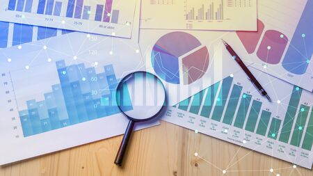 Foto de Magnifying glass and documents with analytics data lying on table,selective focus - Imagen libre de derechos