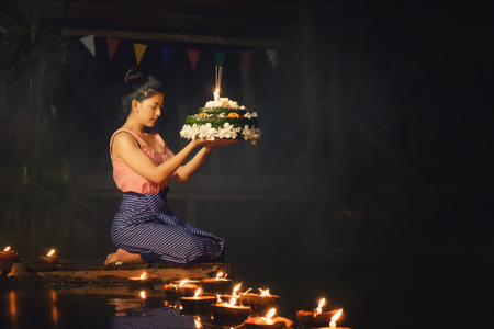 Foto de Loy Krathong Traditional Festival, Thai woman hold kratong, Thailand, Asia woman in Thai dress traditional hold kratong and bring Krathong to float in Loi kratong day of Thailand. - Imagen libre de derechos